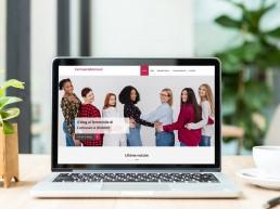 Monitor di computer desktop con homepage del sito: foto di donne