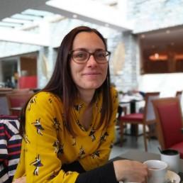 Ragazza con occhiali e maglietta gialla che beve tea